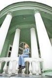 Girl sitting on parapet with white columns Stock Image
