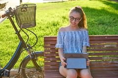 Girl sitting on park bench playing with tablet stock photos