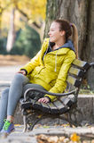 Girl sitting on a park bench Stock Photo