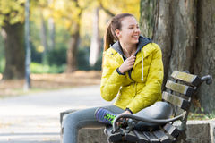 Girl sitting on a park bench Stock Images