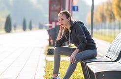 Girl sitting on a park bench Stock Photos