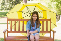Girl sitting on park bench with an umbrella Stock Images