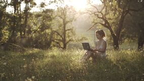 Girl sitting in park or forest, opening laptop on nature. IT specialist working at self isolation outdoors. Woman