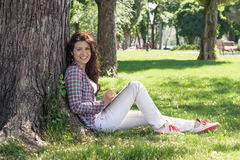 Girl sitting in the park on the grass and draws. Royalty Free Stock Photos