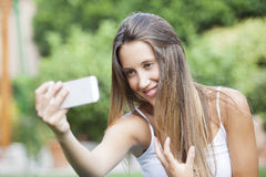 Girl sitting in the park and makes selfie Royalty Free Stock Photography