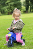Girl sitting in the park on a motorbike Stock Photo