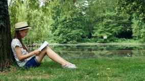 Girl sitting in the park near the lake under the tree and reading a book. Young girl a straw hat sits in the park under the tree and reads a book on a sunny day stock video