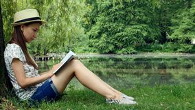 Girl sitting in the park near the lake under the tree and reading a book. Young girl a straw hat sits in the park under the tree and reads a book on a sunny day stock footage