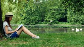 Girl sitting in the park near the lake under the tree and reading a book. Young girl a straw hat sits in the park under the tree and reads a book on a sunny day stock video footage