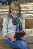Girl sitting in the park and read e-books. Smiling blond colorful scarf royalty free stock image