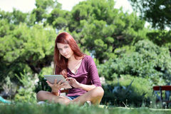 Girl sitting in the park studying with tablet Stock Photos