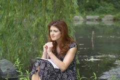 Girl sitting in park thinking. Girl sits in Central Park with a look of despair.  She was in her twenties at the time of shoot and is Jewish american.  she has Royalty Free Stock Photo