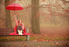 Girl sitting in park with umbrella Stock Photos