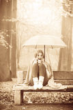 Girl sitting in park with umbrella Stock Images