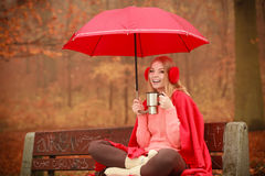Girl sitting in park with umbrella Royalty Free Stock Image