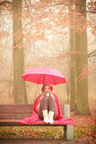 Girl sitting in park with umbrella Royalty Free Stock Photo