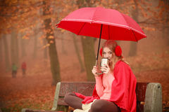 Girl sitting in park with umbrella Stock Photography
