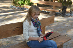 Girl sitting in the park. On a wooden bench and looking at the tablet Stock Photo