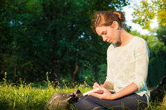 Girl sitting in a park and writing in a notebook. Young beautiful girl sitting in a park and writing in a notebook Royalty Free Stock Images