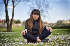 Girl Sitting in the Park. Young girl enjoying a spring day in the park Royalty Free Stock Photography