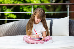 Girl sitting on patio with notepad Royalty Free Stock Photo