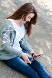 Girl sitting on pavement with tablet. Stock Photo