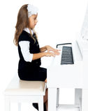 Girl sitting at the piano. Beautiful little girl in the music school, learning to play the piano . the girl looks directly on the keys - Isolated on white Royalty Free Stock Images