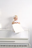 Girl sitting on piano in room Royalty Free Stock Image