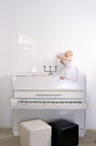 Girl sitting on piano in the room royalty free stock photo