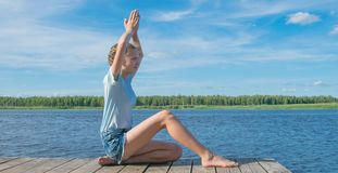Girl sitting on the pier, doing yoga, against the water and sky, there is a place for the inscription royalty free stock photography