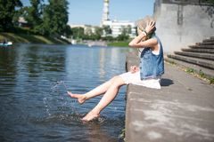 Girl sitting at the pier and hanging bare feet Royalty Free Stock Photos