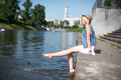 Girl sitting at the pier and hanging bare feet Royalty Free Stock Photo