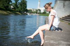 Girl sitting at the pier and hanging bare feet Royalty Free Stock Images
