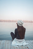 Girl sitting on pier and looking at the river Stock Images