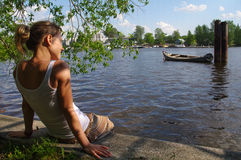 Girl sitting on pier and looking at the river. Woman relaxing by a lake. Stock Image