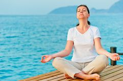 Girl sitting on a pier in lotus position Stock Images