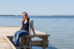 Girl sitting on a pier at the river bank Stock Photography
