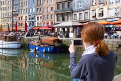 Girl taking a shot of Honfleur harbor Stock Images