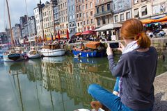 Girl taking a shot of Honfleur harbor Stock Photography