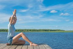 Girl sitting on the pier, in a yoga pose, on the background of nature stock photography