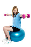 Girl sitting on pilates ball and doing dumbbells Stock Photography