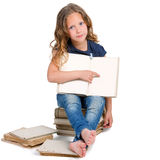 Girl sitting on pile of old books. Stock Photos