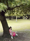 Girl (7-9) sitting on pink space hopper beneath tree in park, smiling, side view Stock Photos