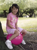 Girl (7-9) sitting on pink space hopper beneath tree in park, smiling, side view, portrait Stock Images