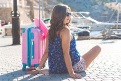 Girl is sitting with pink suitcase Stock Photography