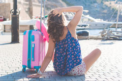 Girl is sitting with pink suitcase Stock Photo