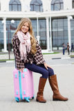 Girl is sitting on pink travel bag over airport Stock Photos