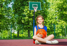 Girl sitting on the playground with ball Royalty Free Stock Photography