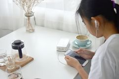 A girl is sitting and playing smartphone in a coffee shop. stock photos