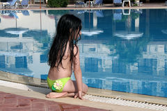 Girl sitting by the pool royalty free stock photography